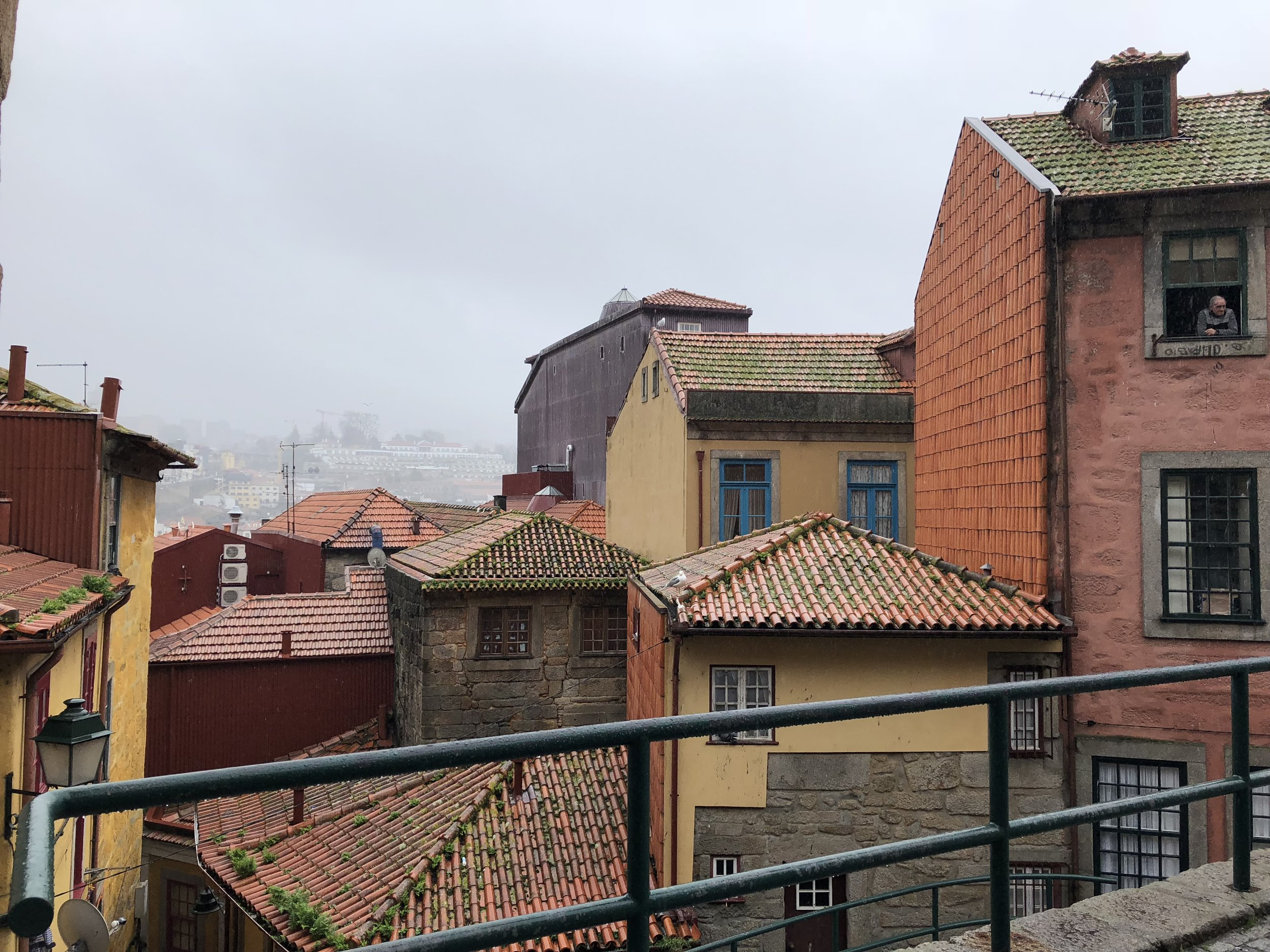 Colorful rooftop shot of Porto on a raining day. Note the local resident smoking out of his window in the top right.