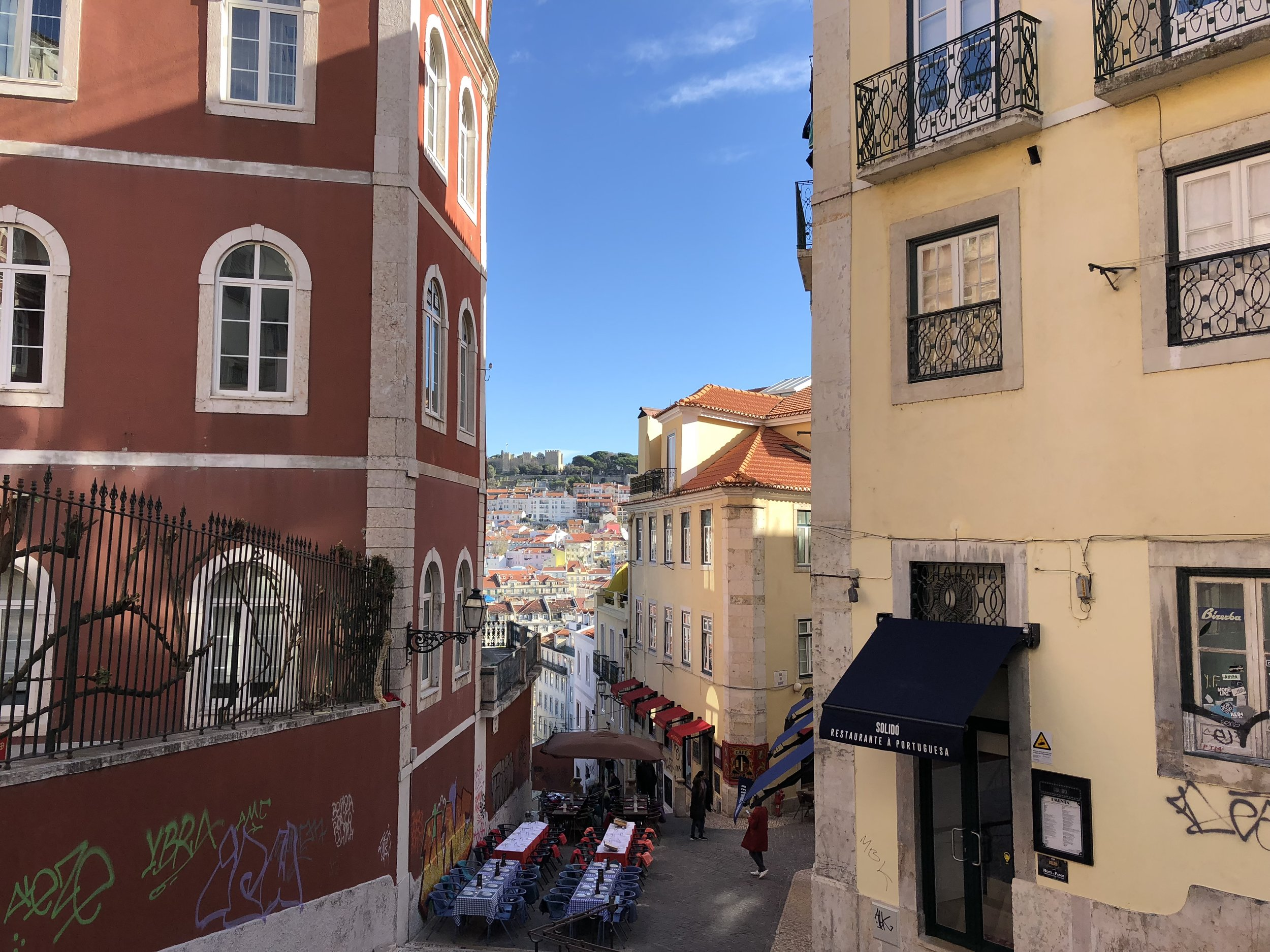 Lisbon's fake castle peeking through an ancient alleyway.
