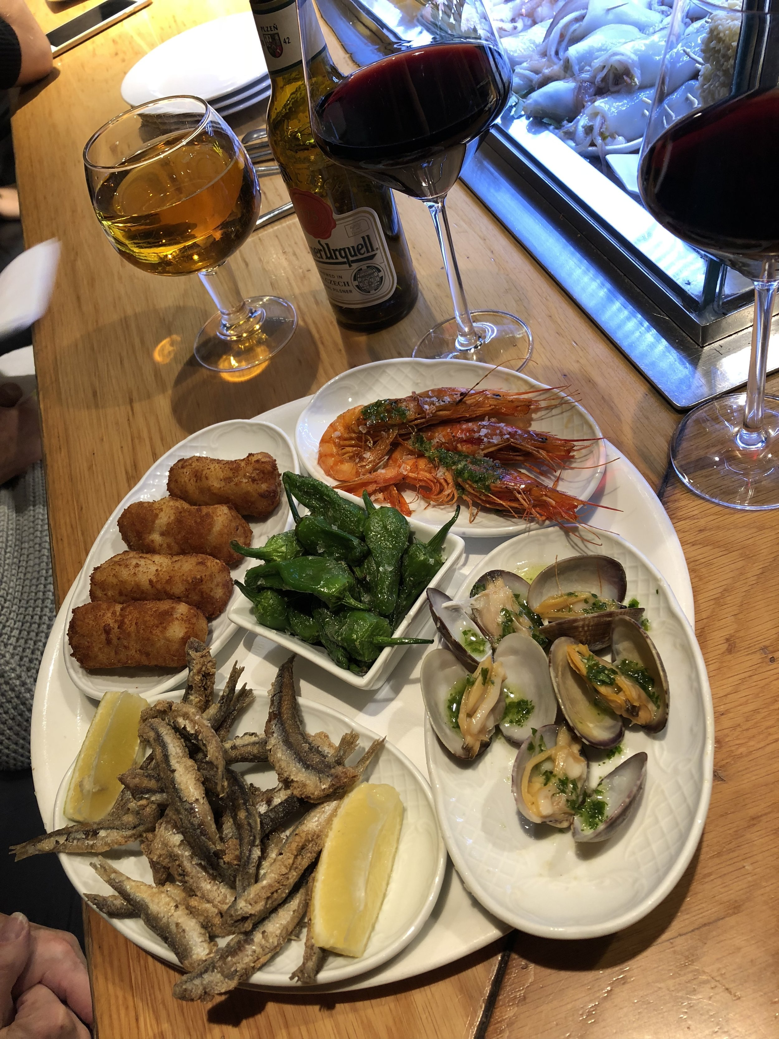 Selection of house tapas at Cerveceria Catalan, including croquettes, shrimp, crispy smelt, poblano peppers, and the best clams we had.