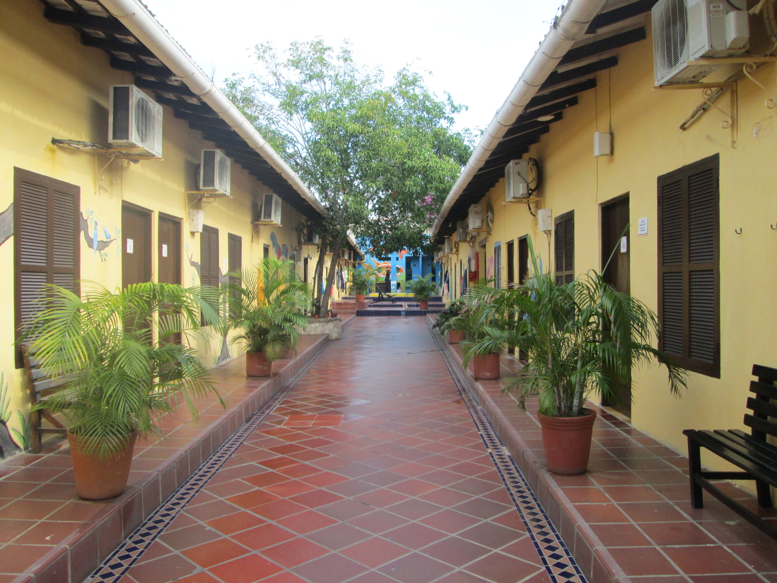 Inside El Viajero Hostel in Cartagena. Rooms line the corridor and culminate in communal bathrooms at the end.