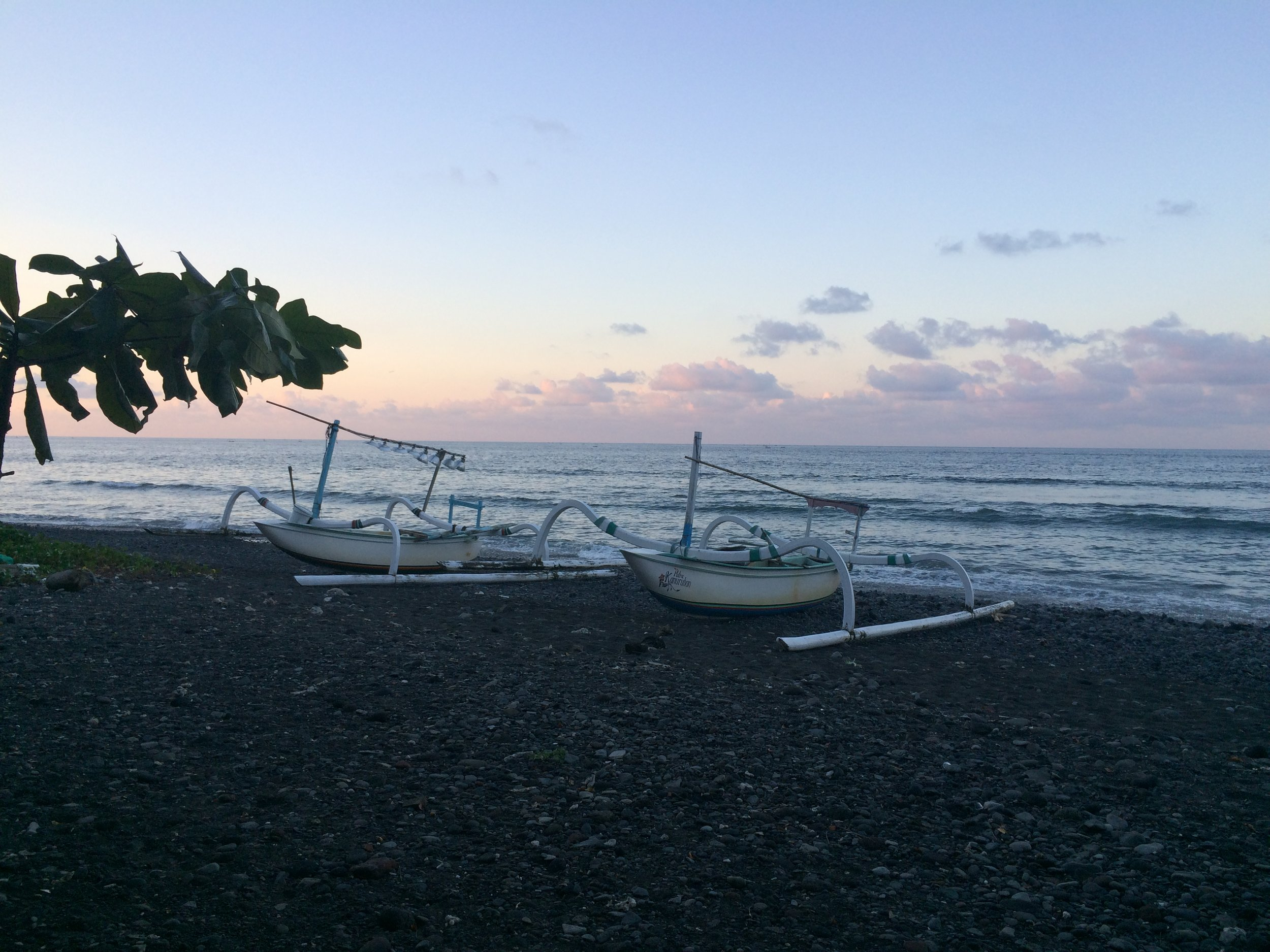 Balinese sunset on the black rock beaches of Amed.