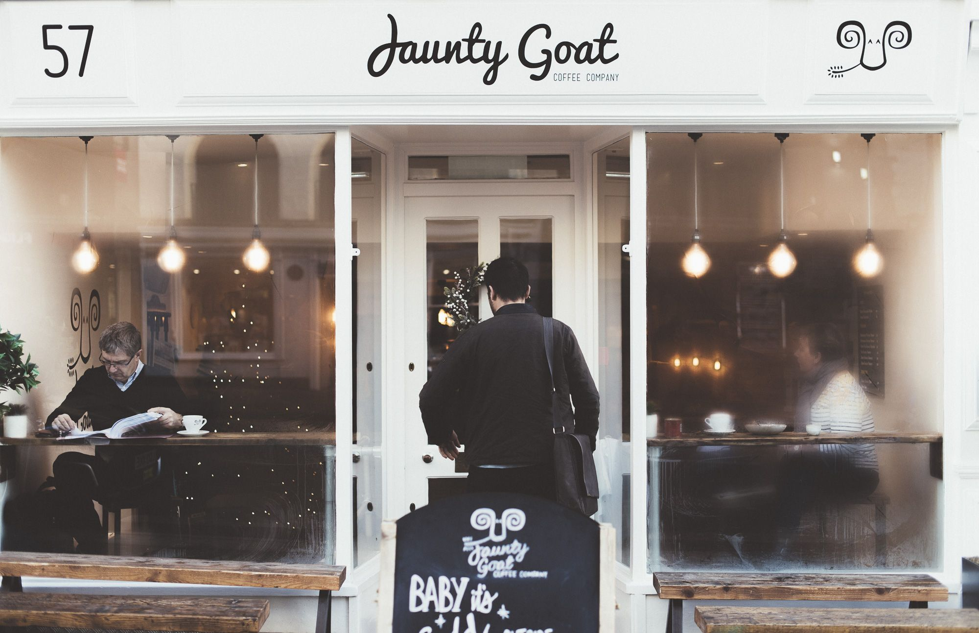Photo of man entering Jaunty Goat Coffee Shop