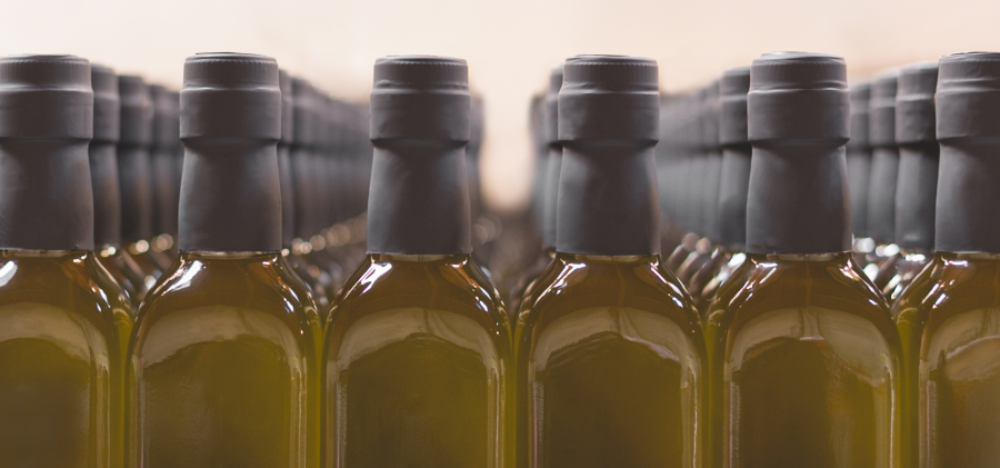 Olive oil filled bottles in a row.