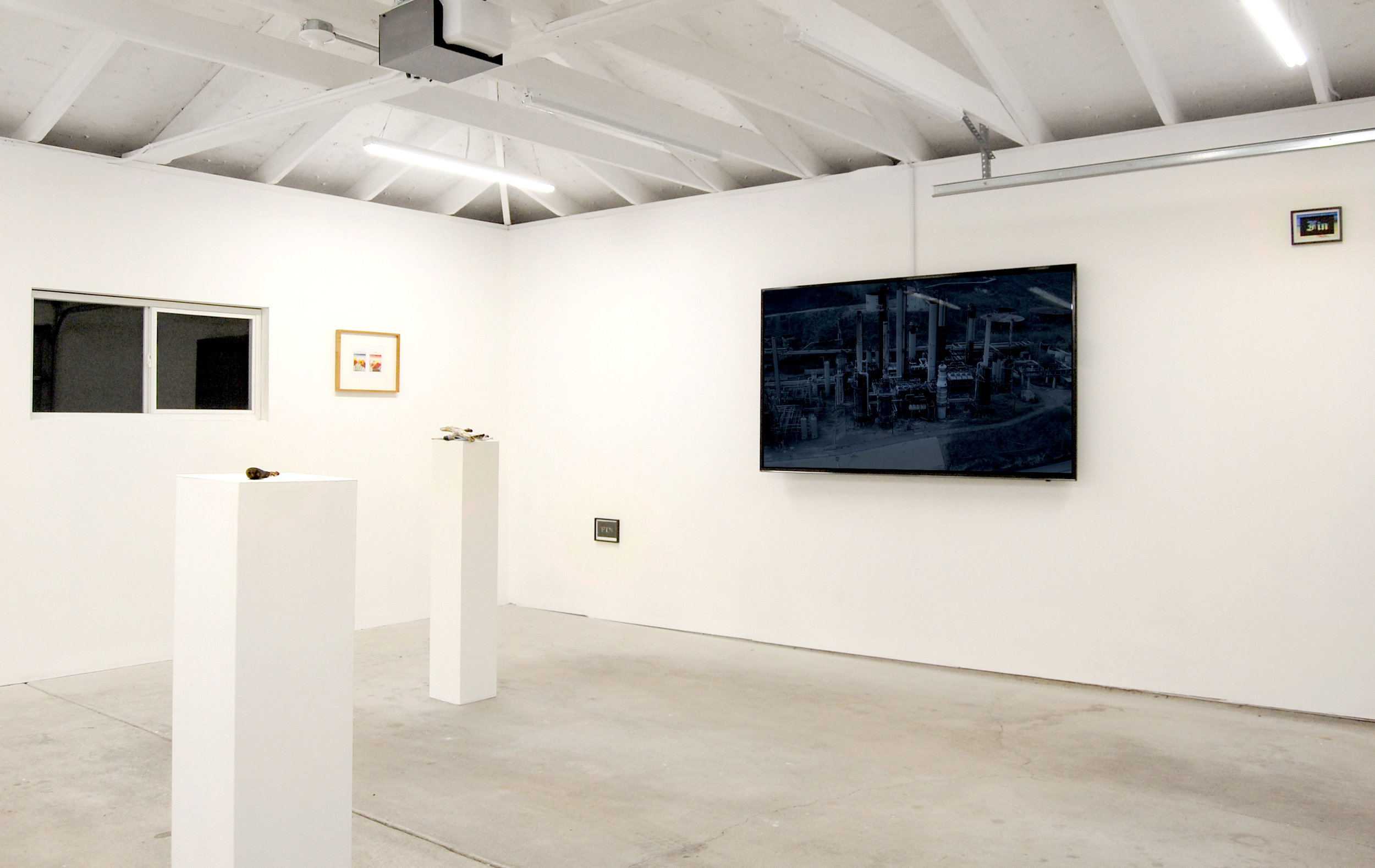 Forced Autumn , installation view at Chicago Manual Style, 2017. From left, Ricardo Morales-Hernández, Drawing instrument, ' Stylus ,' c. 2016–2017, wood and paint, Allora & Calzadilla,  La Noche Que Volvimos a Ser Gente (The Night We Became People Again) , 2017. Digital HD colour video with sound, Courtesy Gladstone Gallery, Brussels and New York, and CARNE Adriana Martínez,  FIN Postcard , 2017, vinyl on postcard.