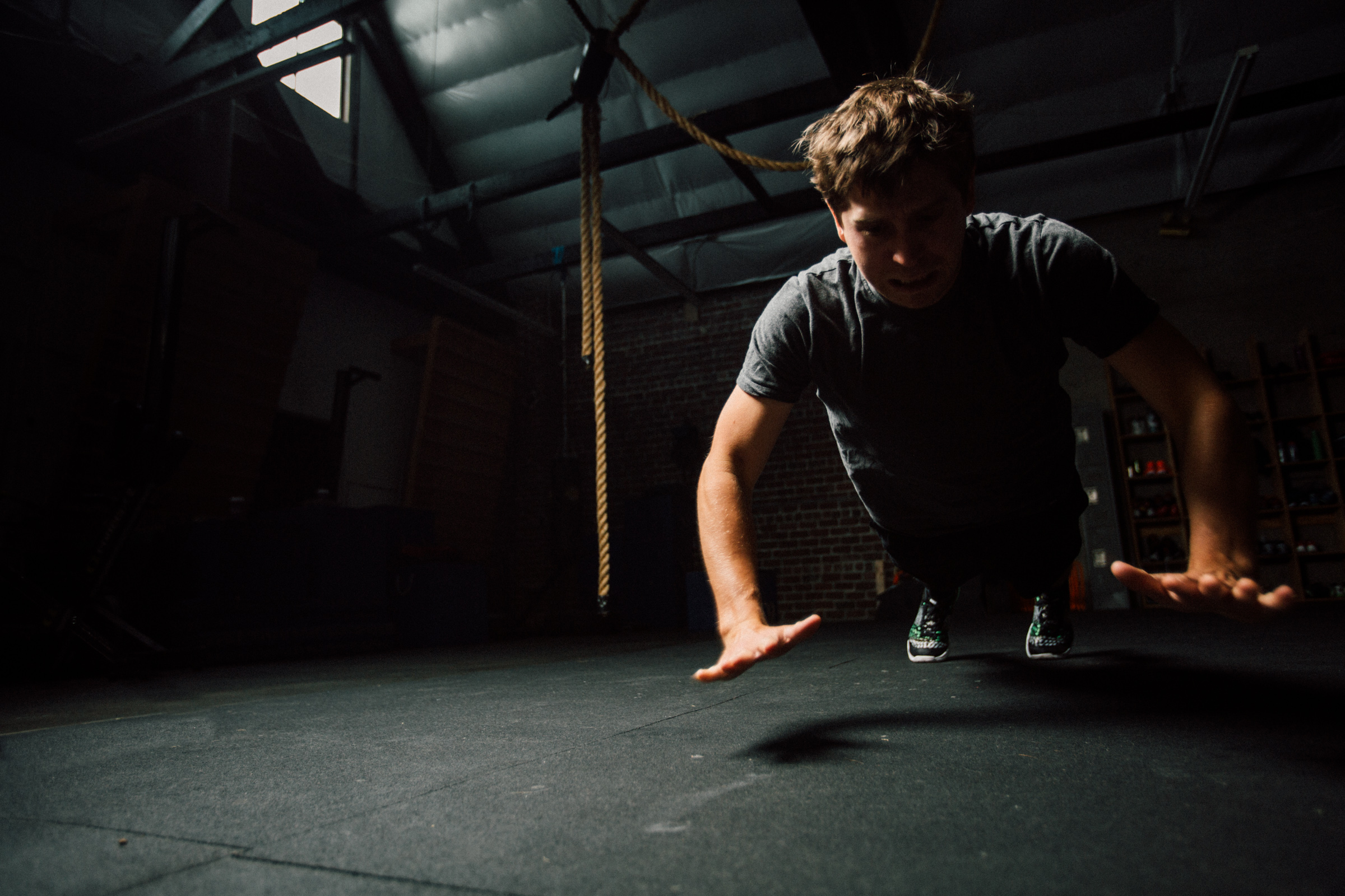 Dramatic lighting hide distracting elements in the gym allowing viewers eyes to move toward the subject.