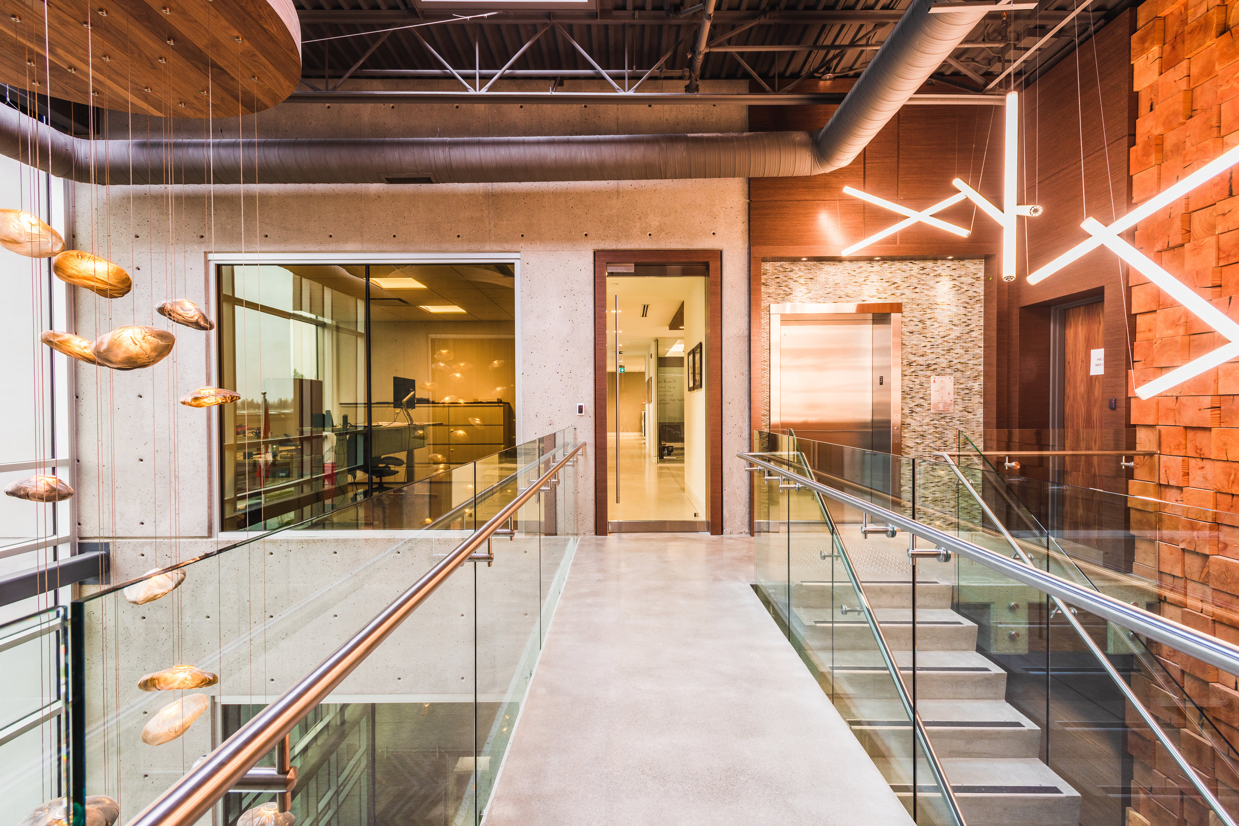 commercial head office hallway made of concrete, reclaimed wood, and bocci lighting