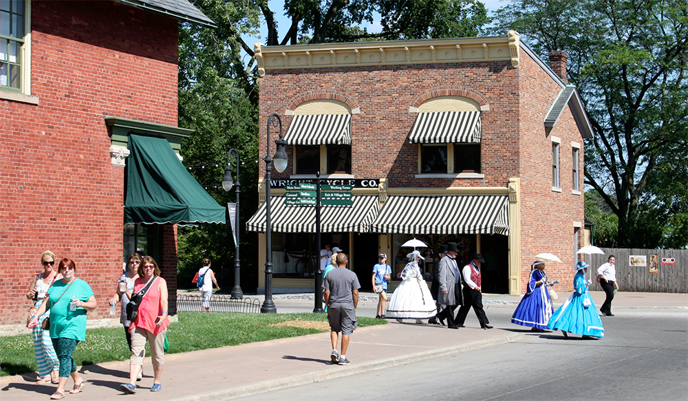 Costumed historical reenactors walk down Main Street.
