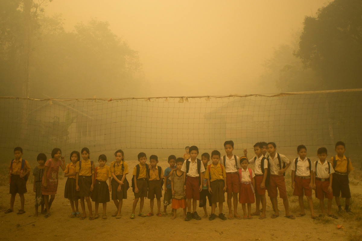 Photo: Children play in thick haze from the forest fires at Sei Ahass village, Borneo island, Indonesia. Ardiles Rante / Greenpeace