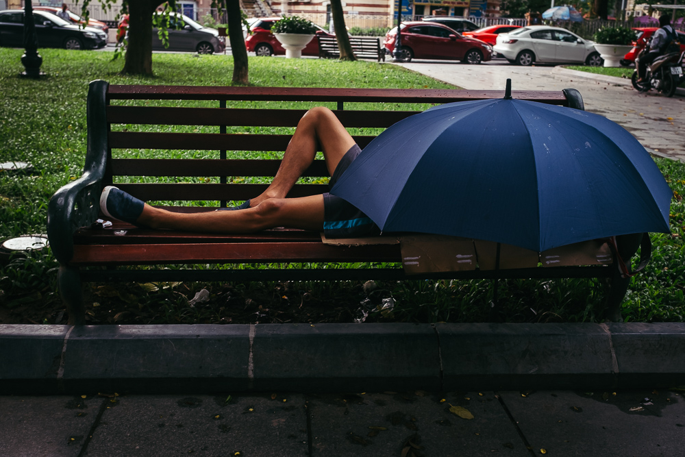 Man sleeping under an umbrella in a park in Hanoi