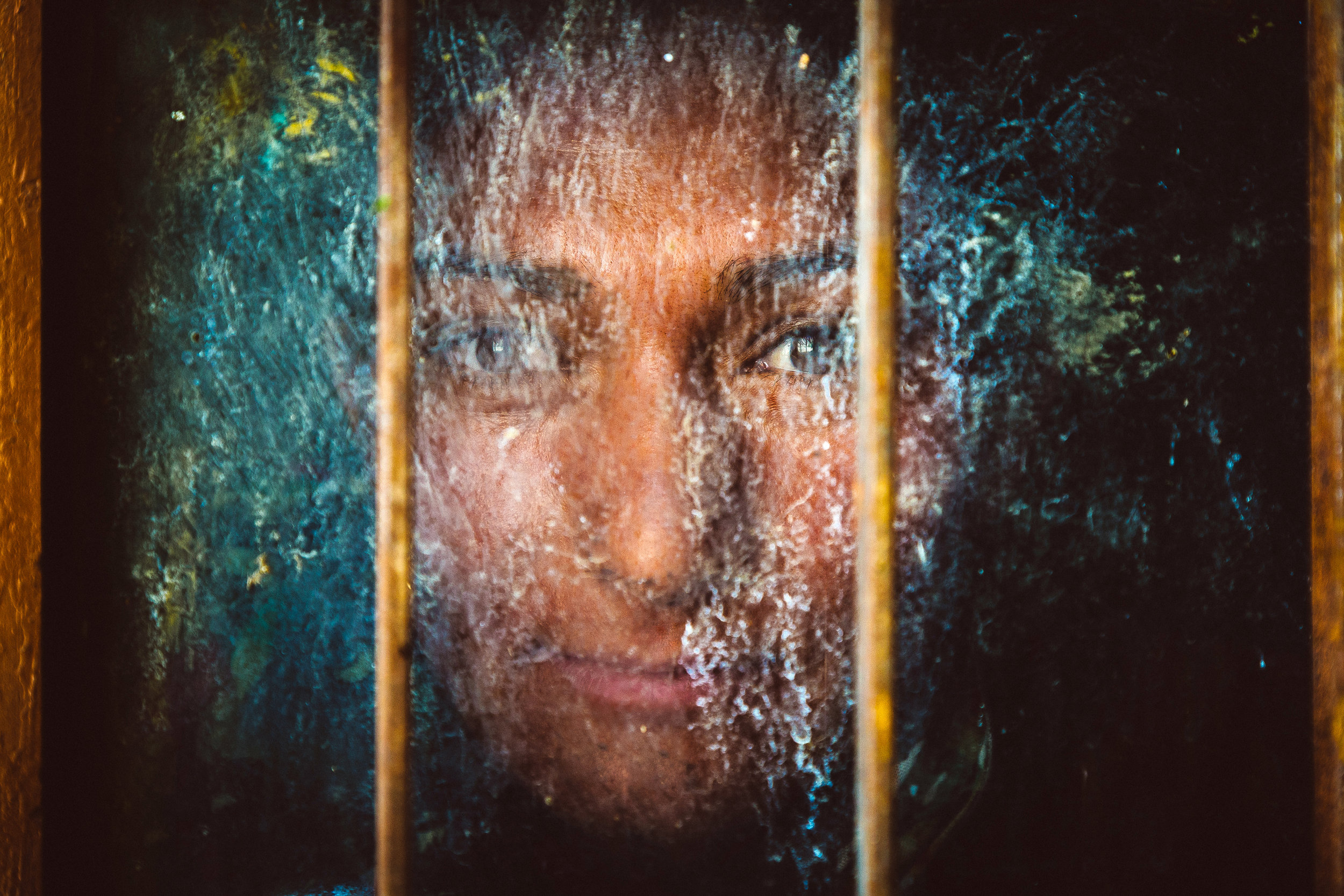 An Aryan woman looking through a dirty old window in an Aryan vi