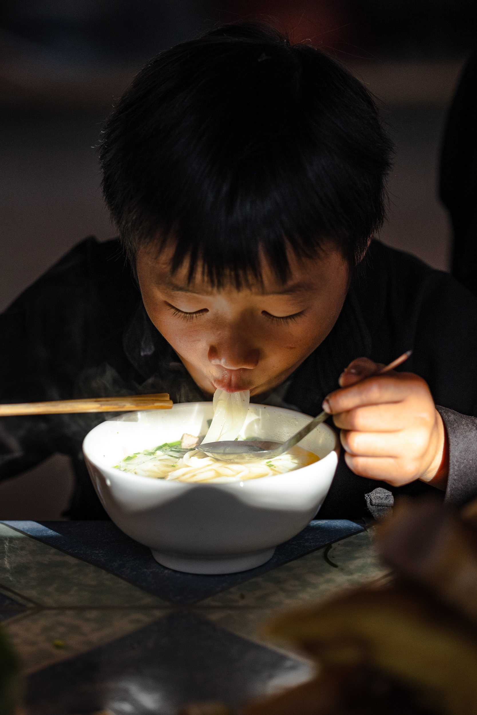 A boy enjoying his pho noodles in Dong van market in Vietnam.