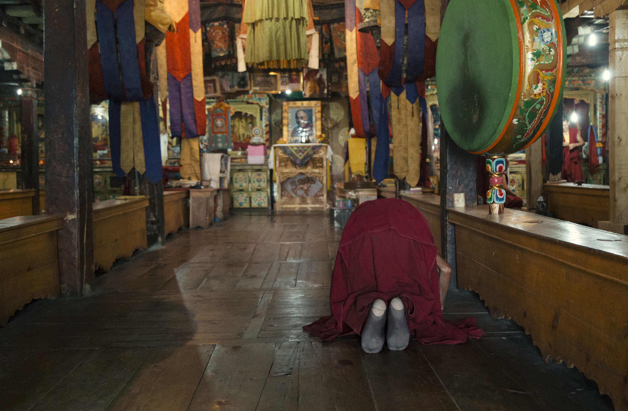 A Buddhist monk praying at the prayer hall in Thiksey monastry
