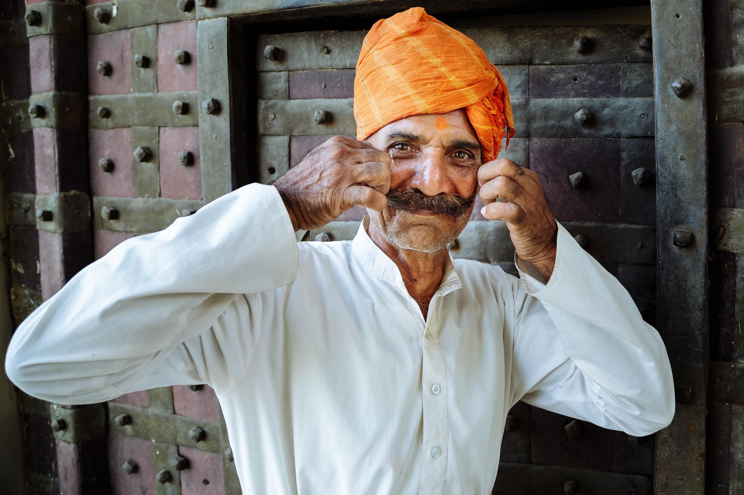 A Rajasthani guard adjusting his mustache near a fort in Mandawa