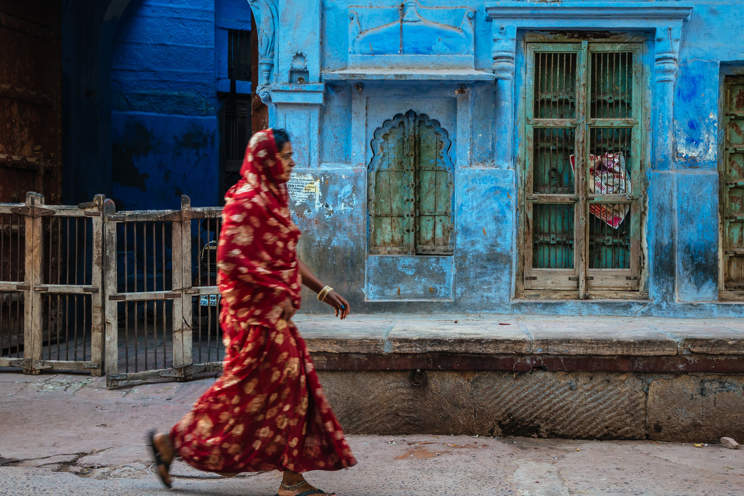 A woman in Red saree walking in the streets of Blue city in Jodh