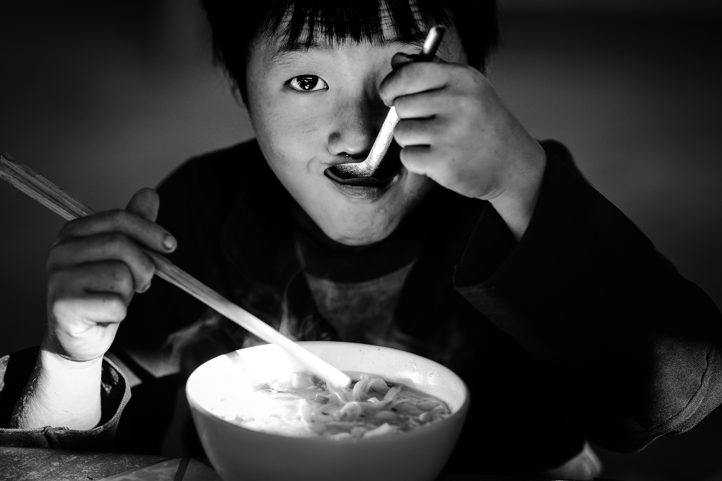 A young boy having pho noodles in Dong van market in northern vi