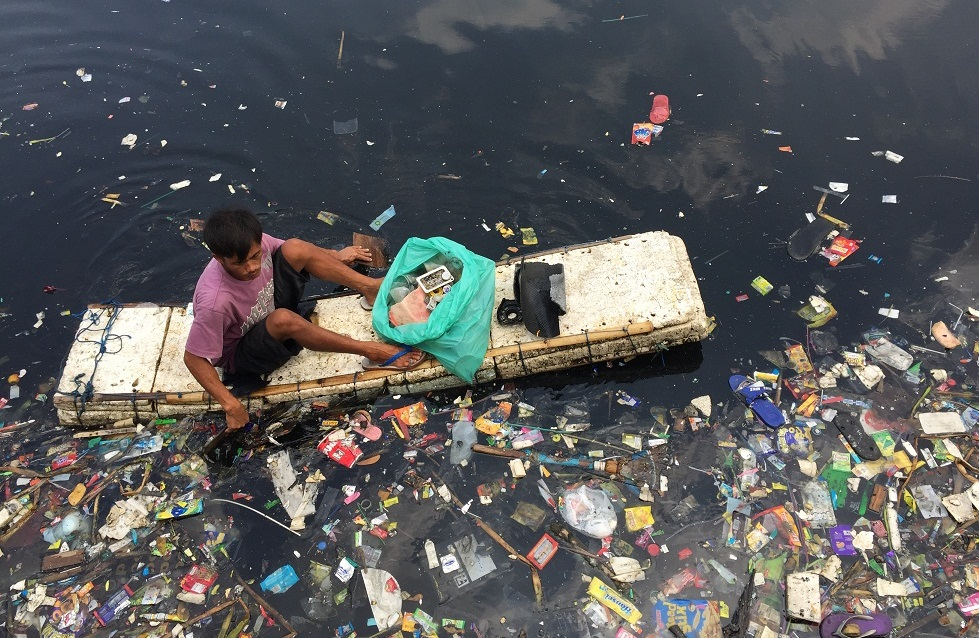 - A man on a make-shift canoe surrounded by floating plastic trash.