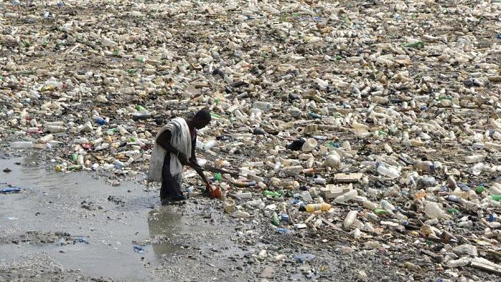 - A man gathers plastic at a waste water evacuation canal in the Ebrie Lagoon, Abidjan.