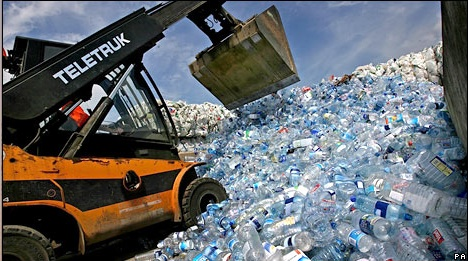 An excavator sifts through a pile of discarded plastic water bottles. Photo from The Acronym.