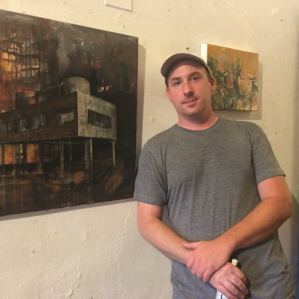 Brendan Day standing outside his studio at the Harrison Center between his oldest (left) and latest artworks.