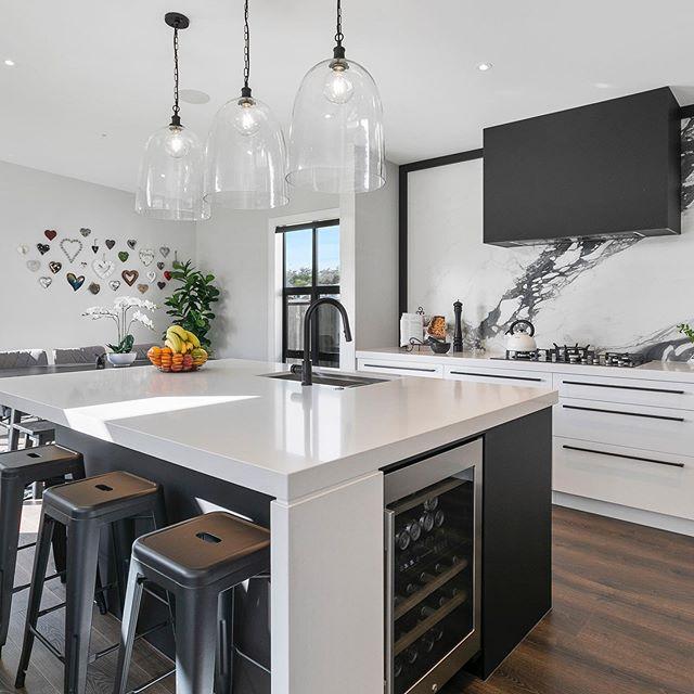 The contemporary black & white kitchen with an artistic tile splash-back...#houseoftheyearnz #Maddren #fluid_interiorsnz #kitcheninspiration #kitchendesign