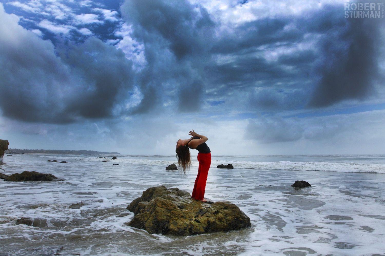 Robert Sturman photography of a yoga pose on a rock near the ocean