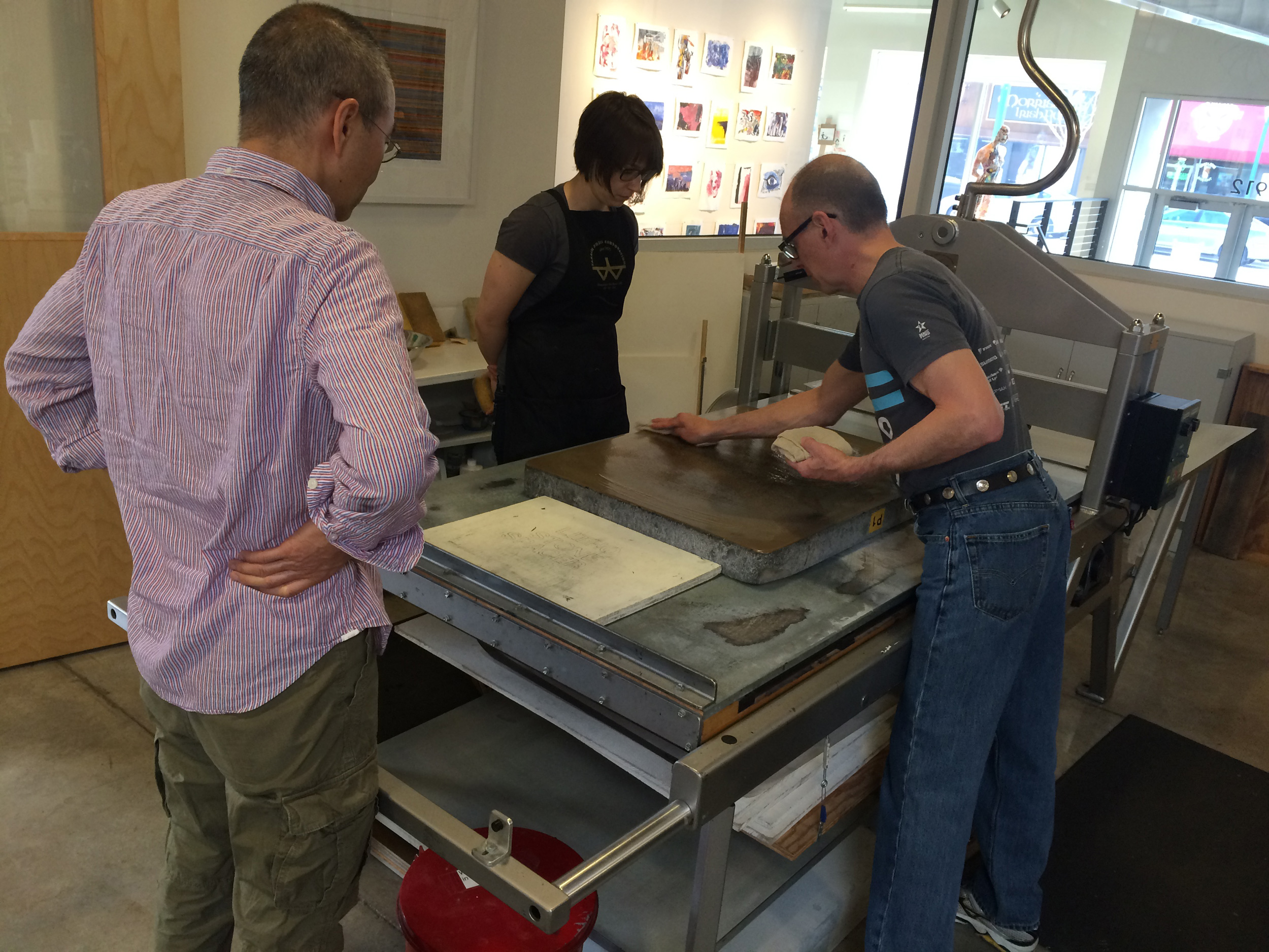 HPE Artist, Do Ho Suh, observing the printing of his stone lithograph