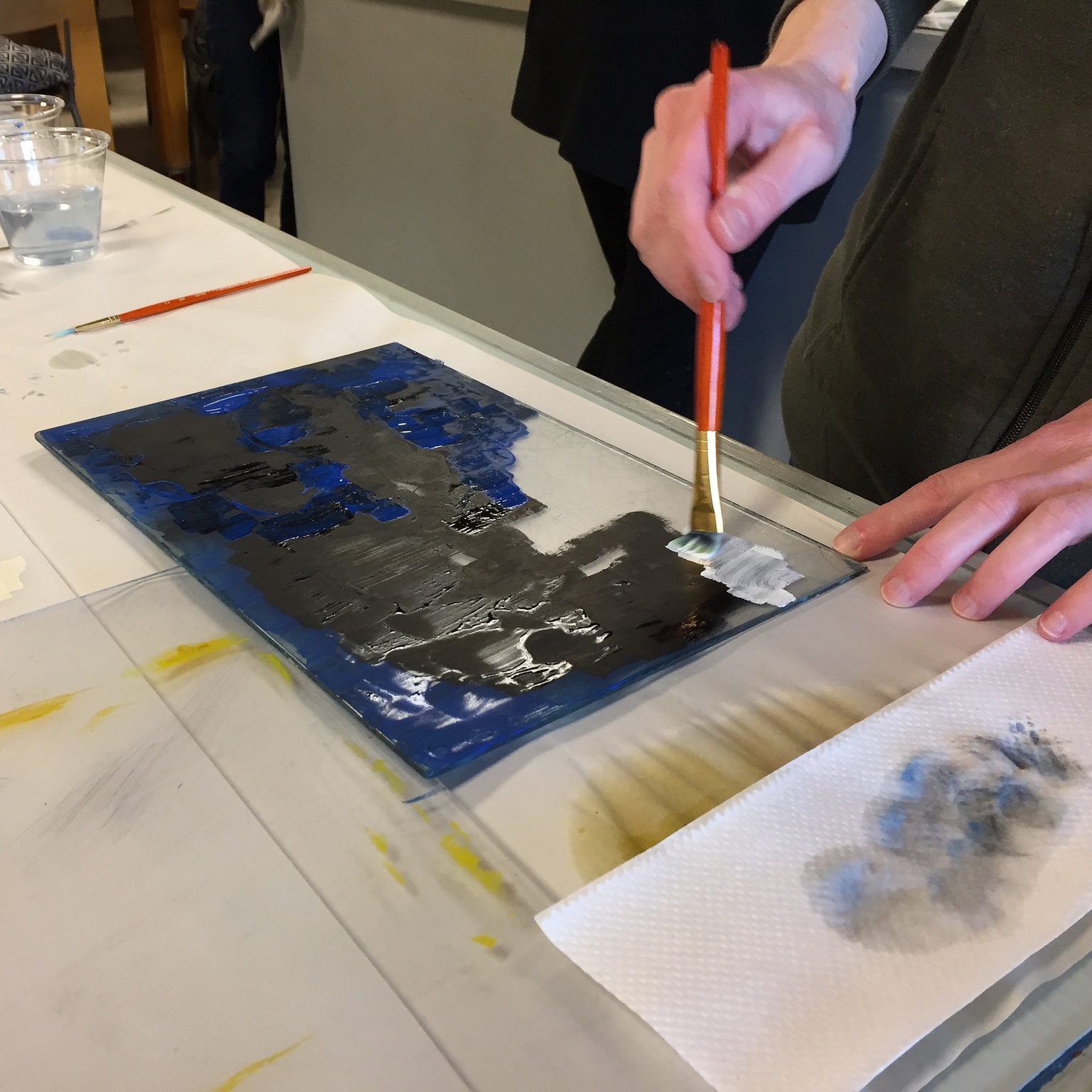 Painting ink onto a plexiglass plate.