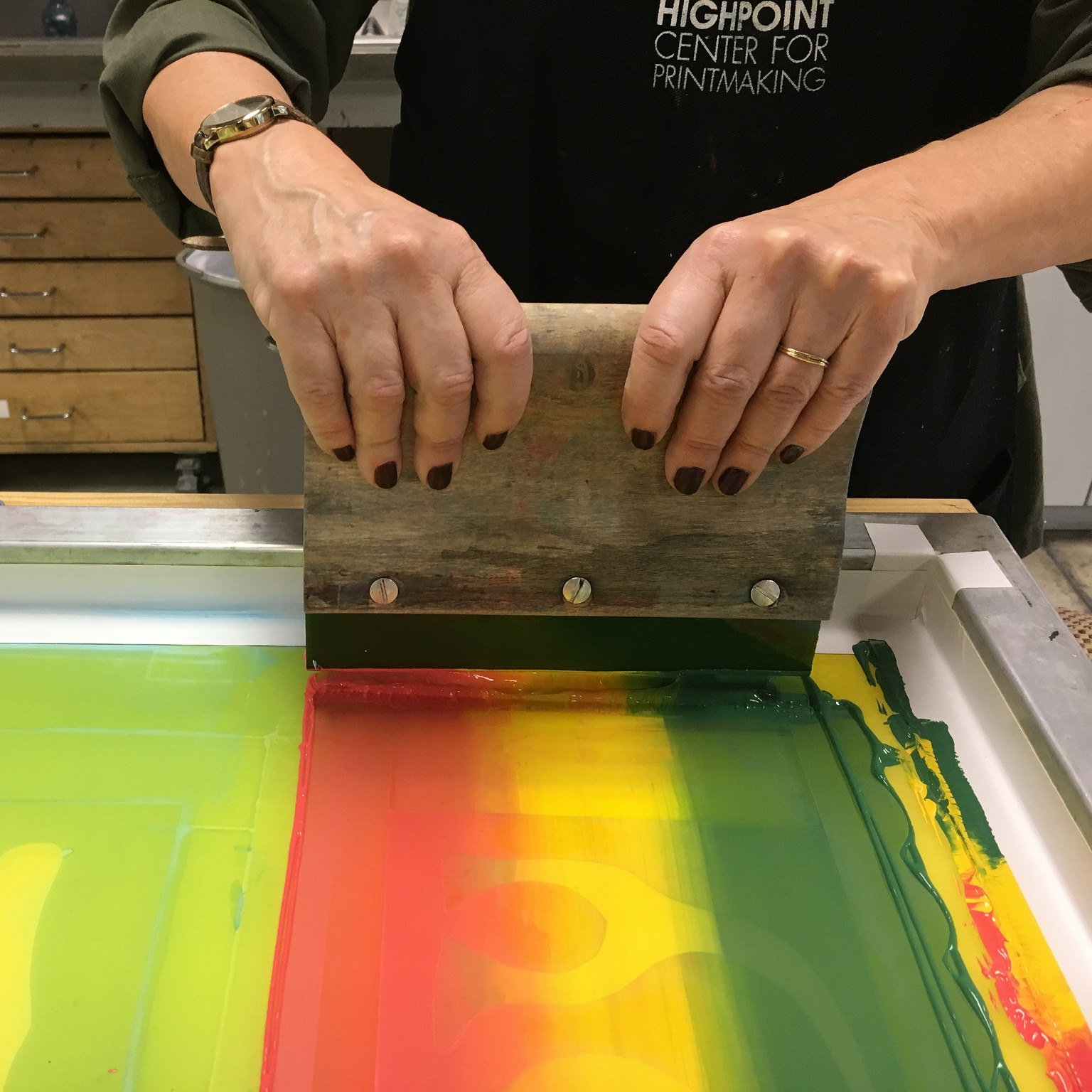Using a squeegee to push ink through a screen onto paper.