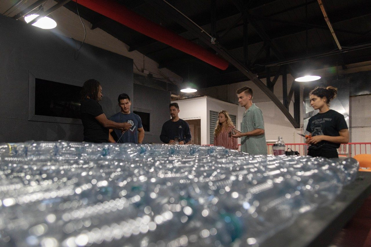 Visiting artist Willie Cole shows Virginia Tech students how to reconfigure plastic bottles for use in a building project. Image credit https://vtnews.vt.edu/