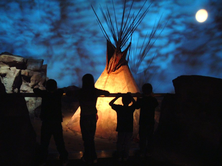 """Visitors in silhouette in front of the """"Seasons of Life"""" gallery in the Plains Indian Museum. Photo credit  centerofthewest.org"""