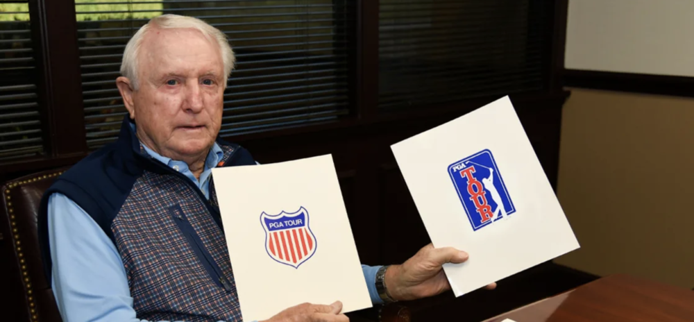 Deane Beman posing with mock-ups of possible PGA Tour logos