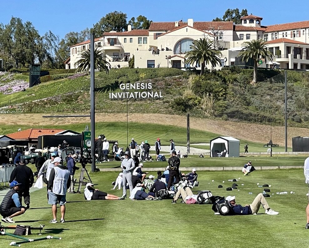 Players and caddies lounge on the range during the play stoppage