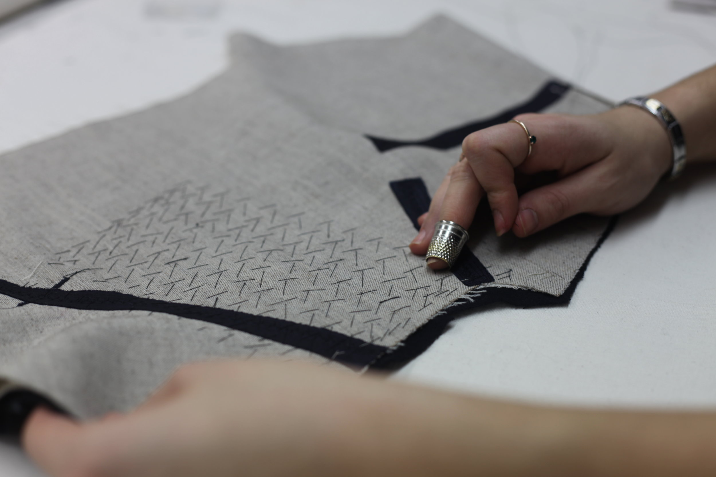 Basting of the garment: in the front of the jacket before moving on to putting the inside and outside pockets, after the stitching of the sides.Interlinings preparation and the laying of the front of the jacket: it represents 600 stitches by hand. The front of the jacket is the suit's most sensitive part. -