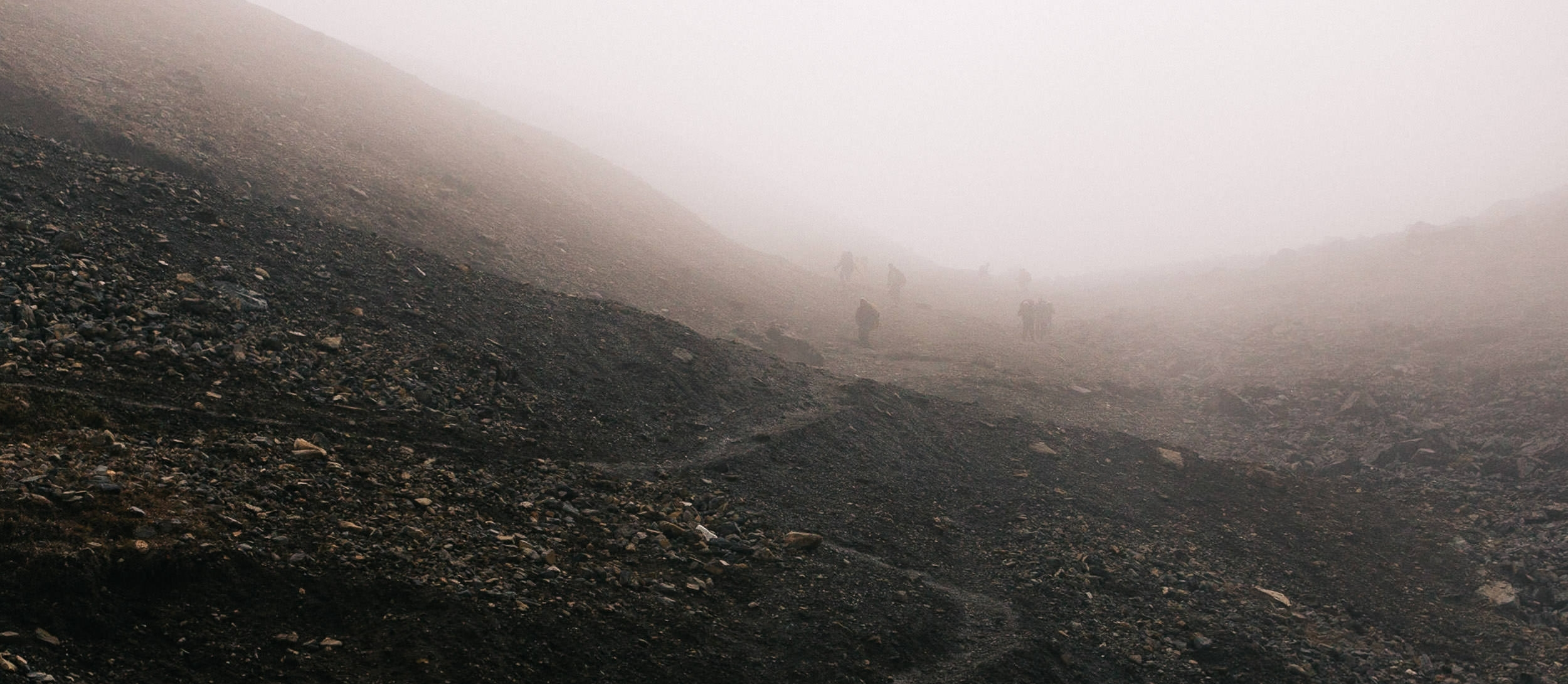 A group of porters descend the Thorong-La Pass through the mist.