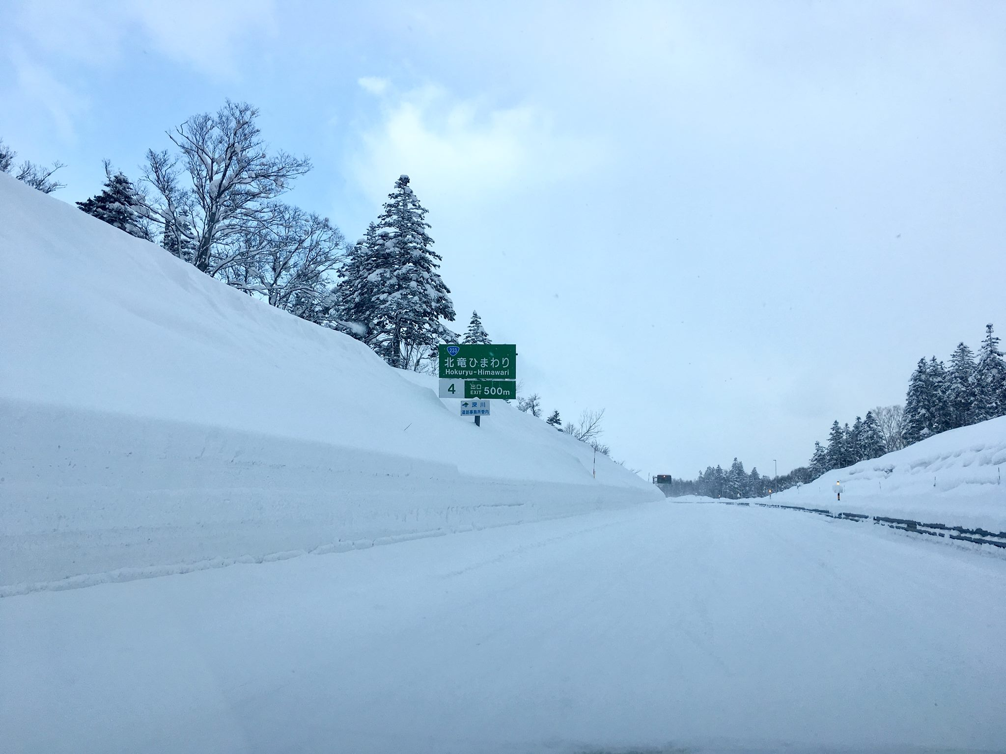 Huge snow banks along the highway and no asphalt to be seen.
