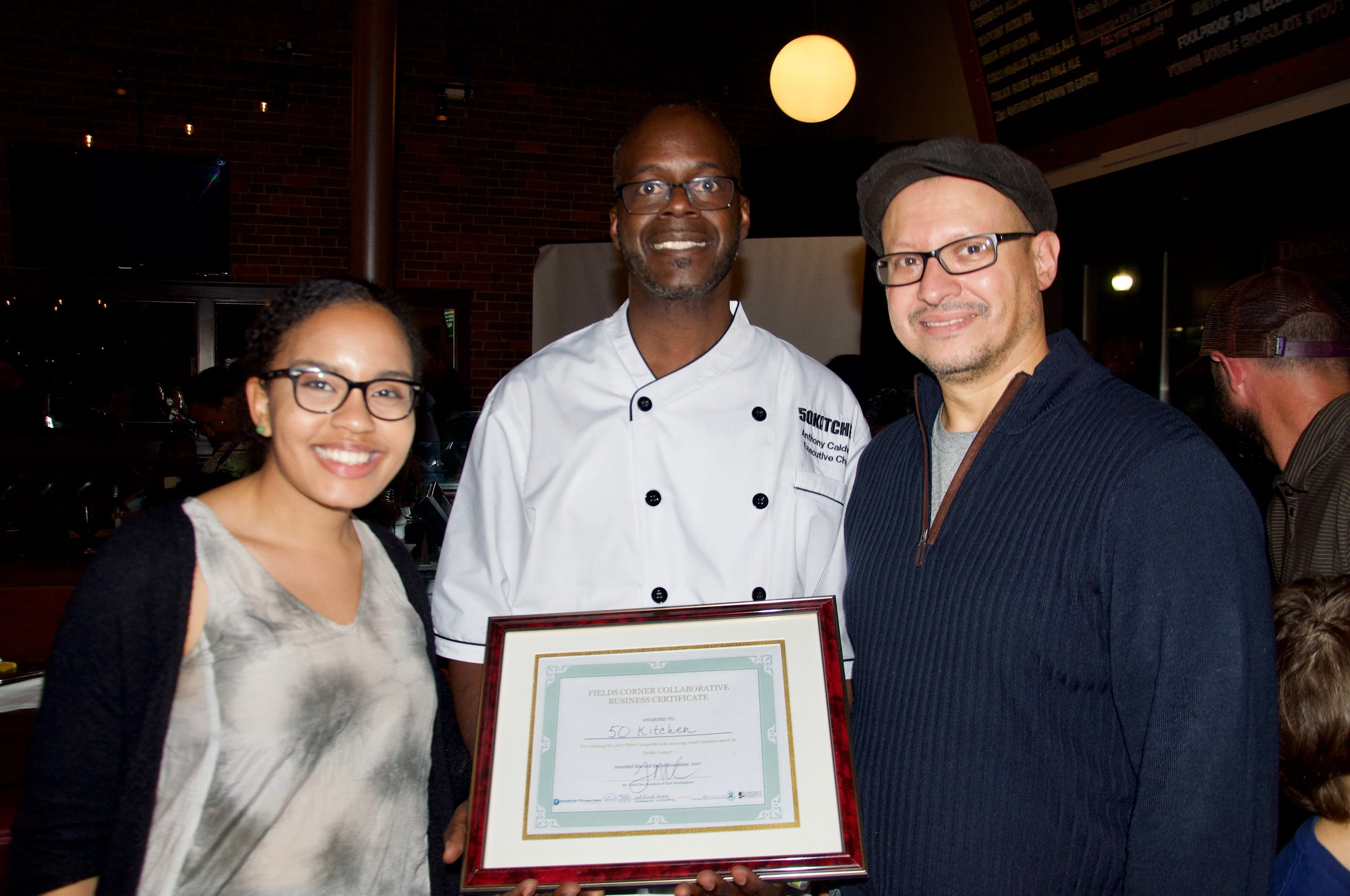 Anthony Caldwell (middle) celebrates with Strategy & Development Director Amine Benali and QVS Fellow Shaina Robinson (Photo by Ben Selden)