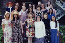 20 women in casual summer attire, lined up in three rows and smiling for the camera.
