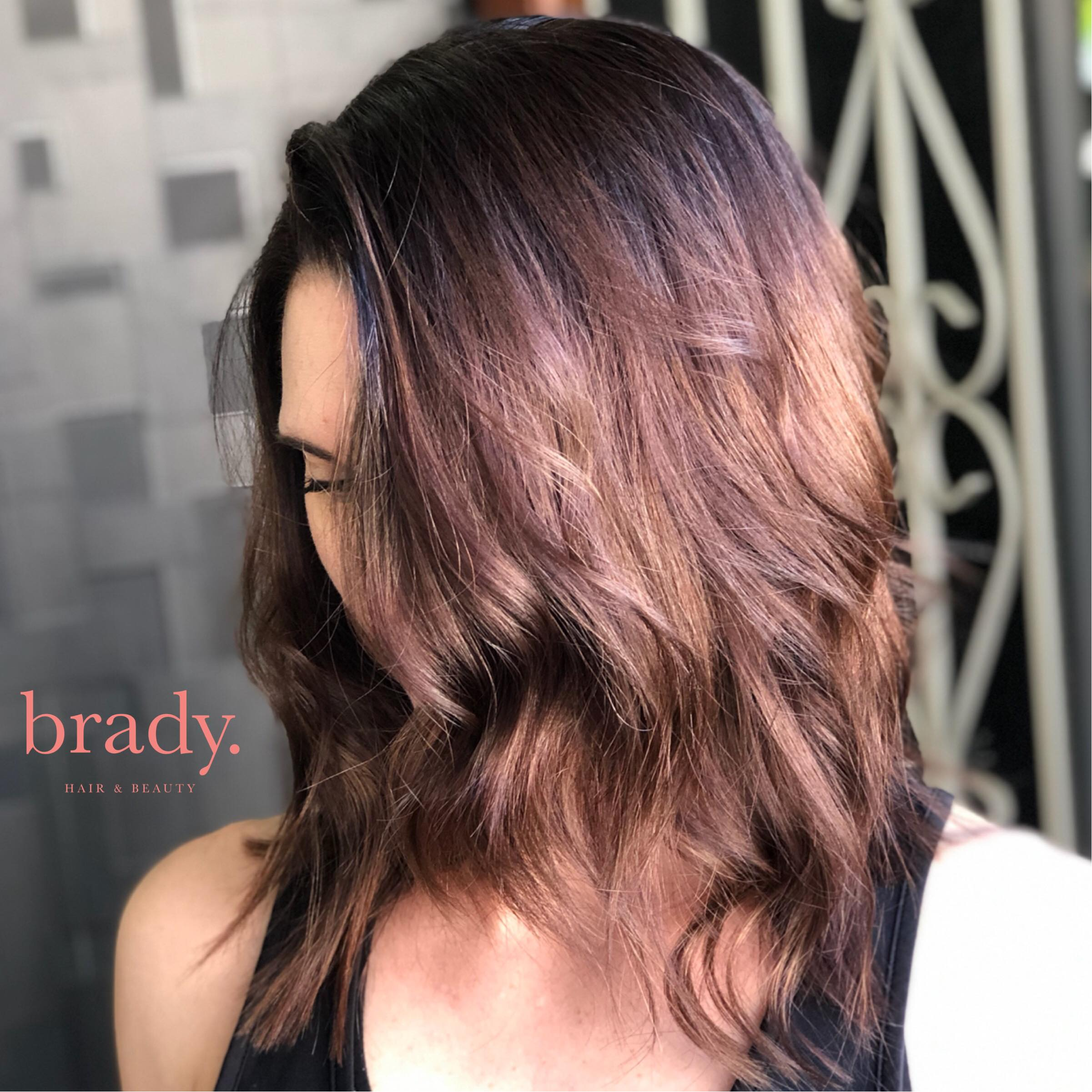Photo of woman with medium-length wavy brunette hair, styled by Brady. Hair & Beauty, Toowong, Brisbane.