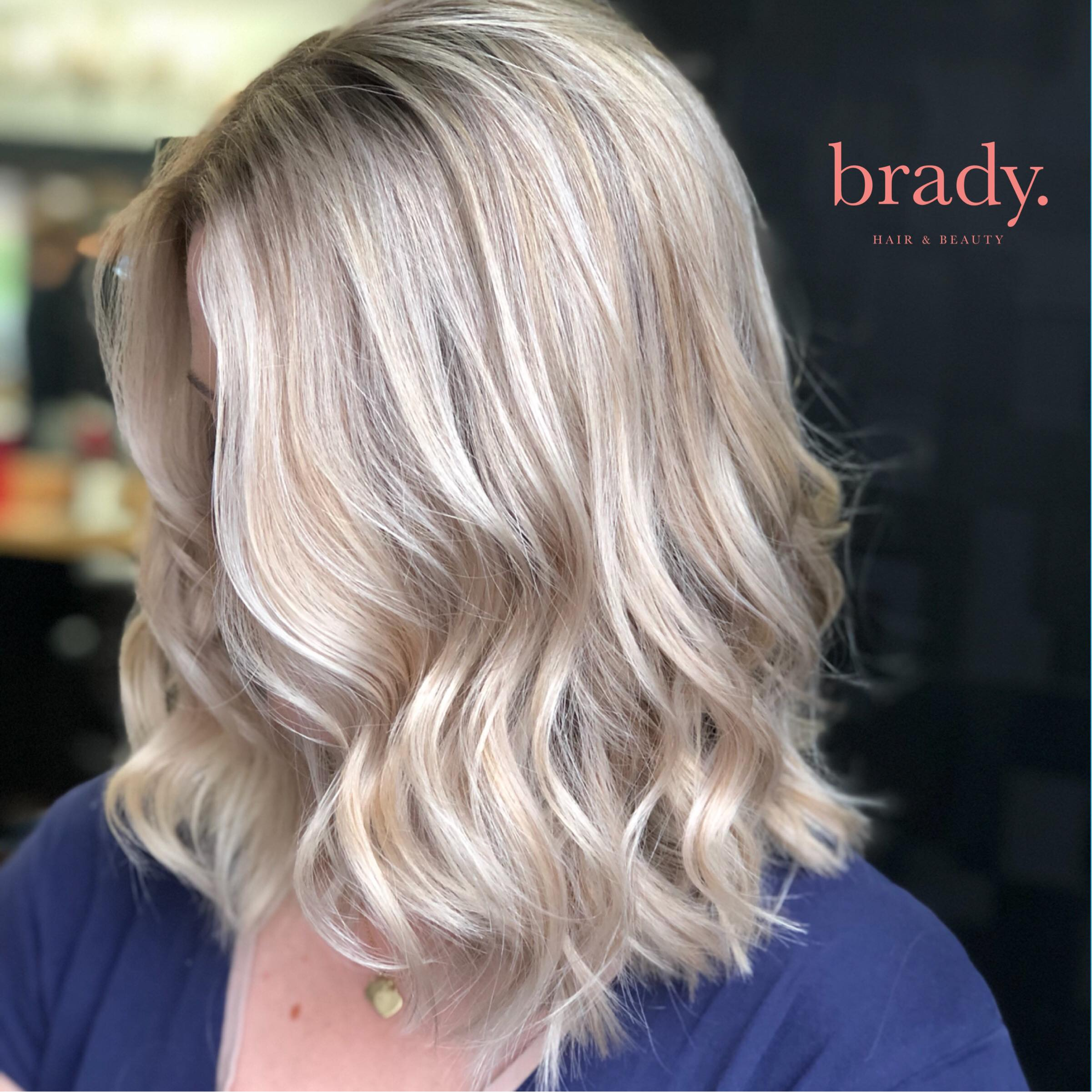 Photo of woman with medium-length, wavy blonde hair styled by Brady. Hair & Beauty, Toowong, Brisbane.