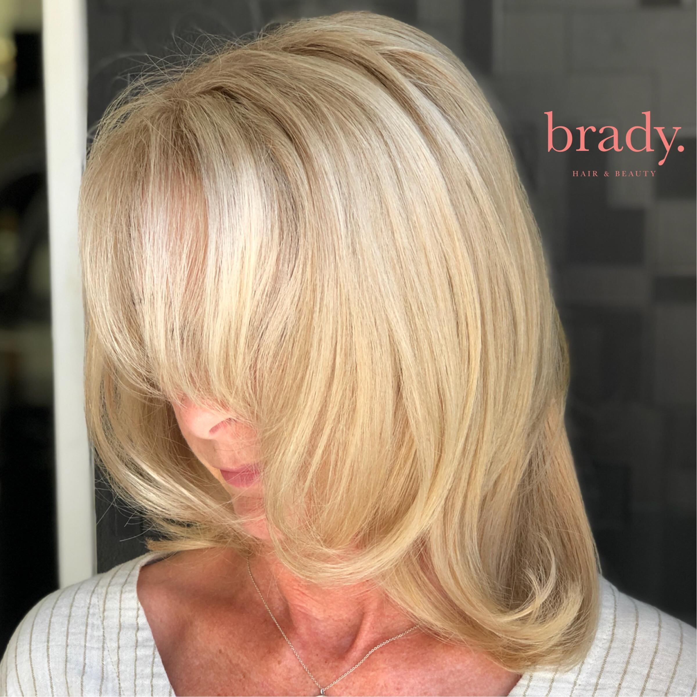 Photo of woman with soft, shoulder length blonde hair, styled by Brady. Hair & Beauty, Toowong, Brisbane.