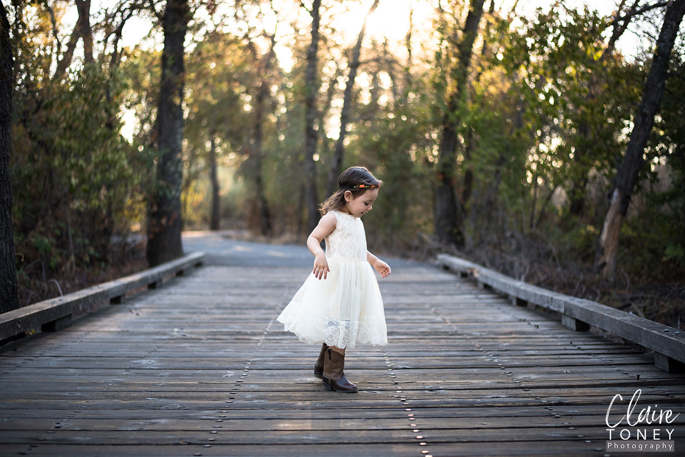 Little girl on a wooden platform wearing boots and a vintage styled dress.