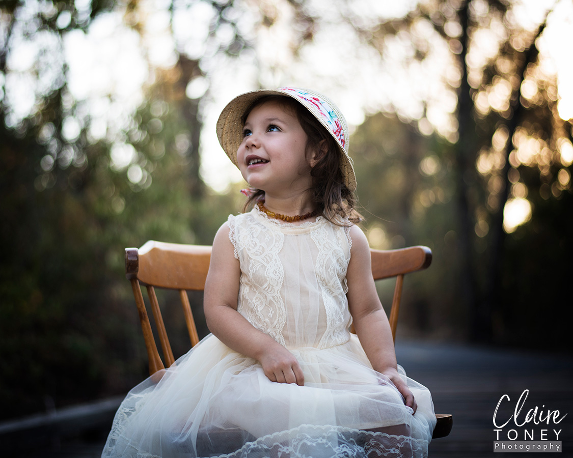 Little girl sitting, wearing a vintage styled dress.