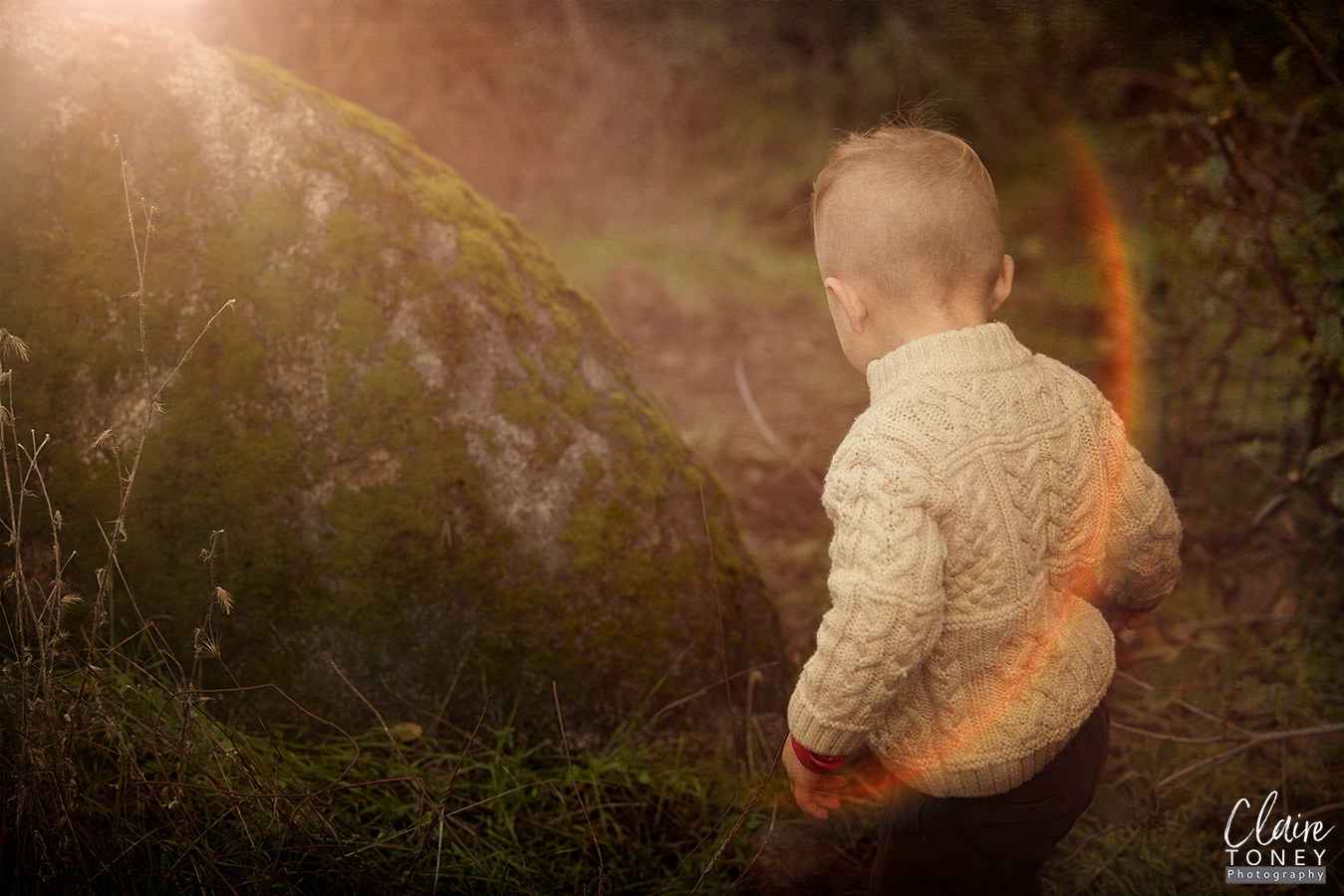 Young boy turned away, with a sun flare on the right side of the photograph.