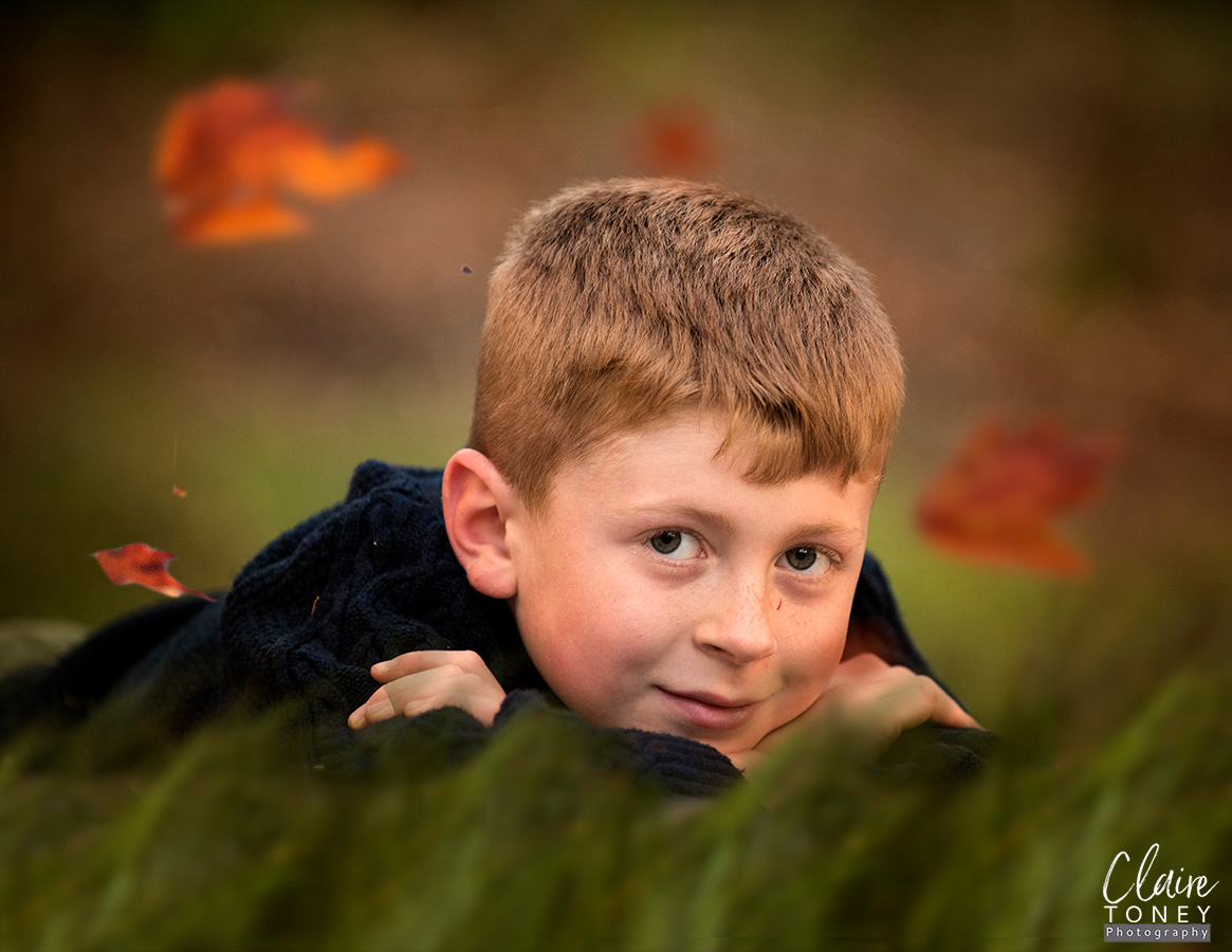Young re-haired boy laying on the ground with leaves floating around him.