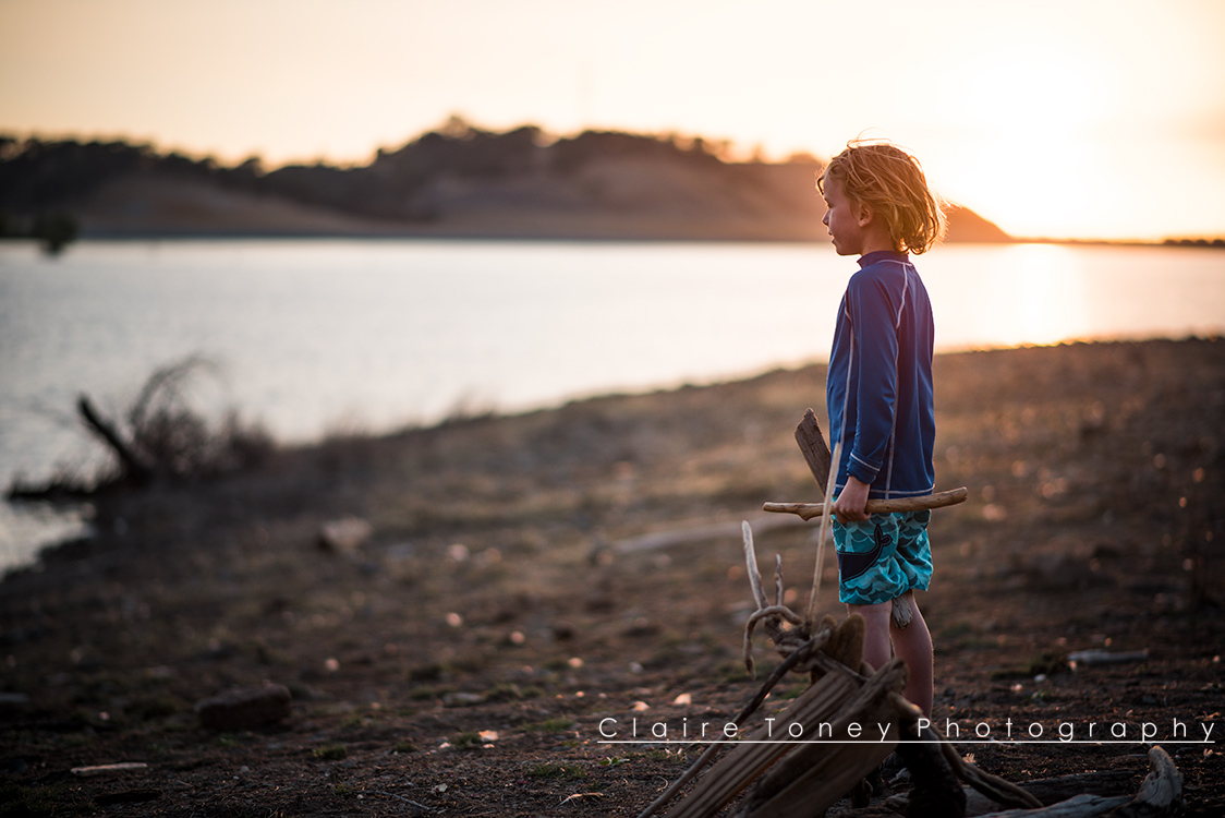 Little boy looking out over Folsom Lake during sunset holding driftwood
