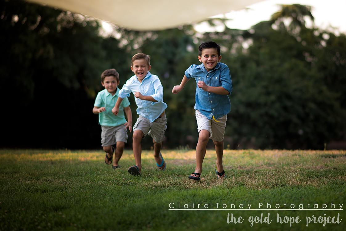 Three boys running on an open green field at the UC Davis Arboretum.
