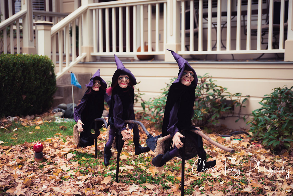 3 purple witch halloween decorations on a leaf strewn lawn, in front of a house with a white fence enclosed porch