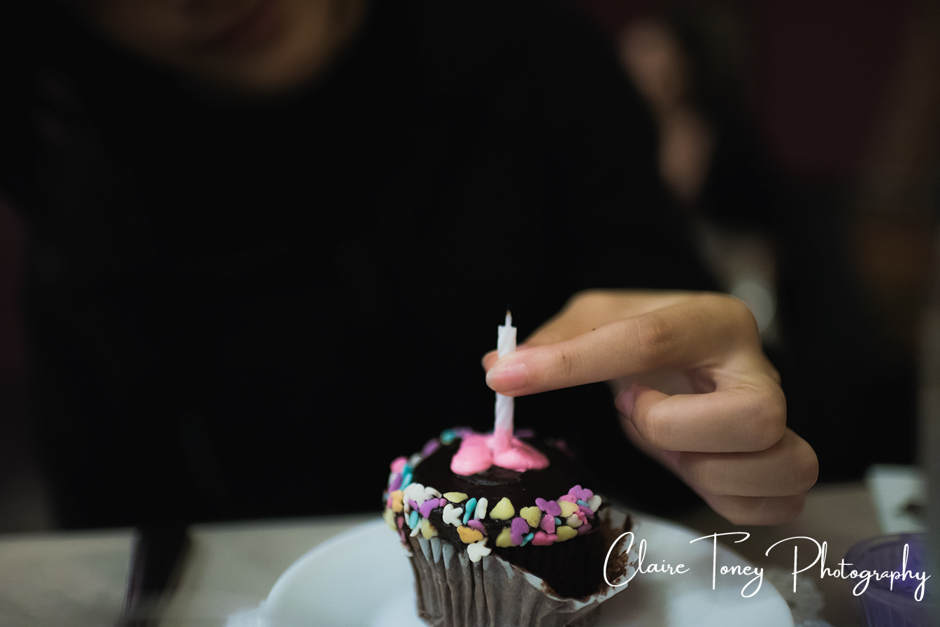 Fingers holding a birthday candle that is on a cupcake at Dash of Panache Teahouse Roseville CA Documentary Photography Claire Toney