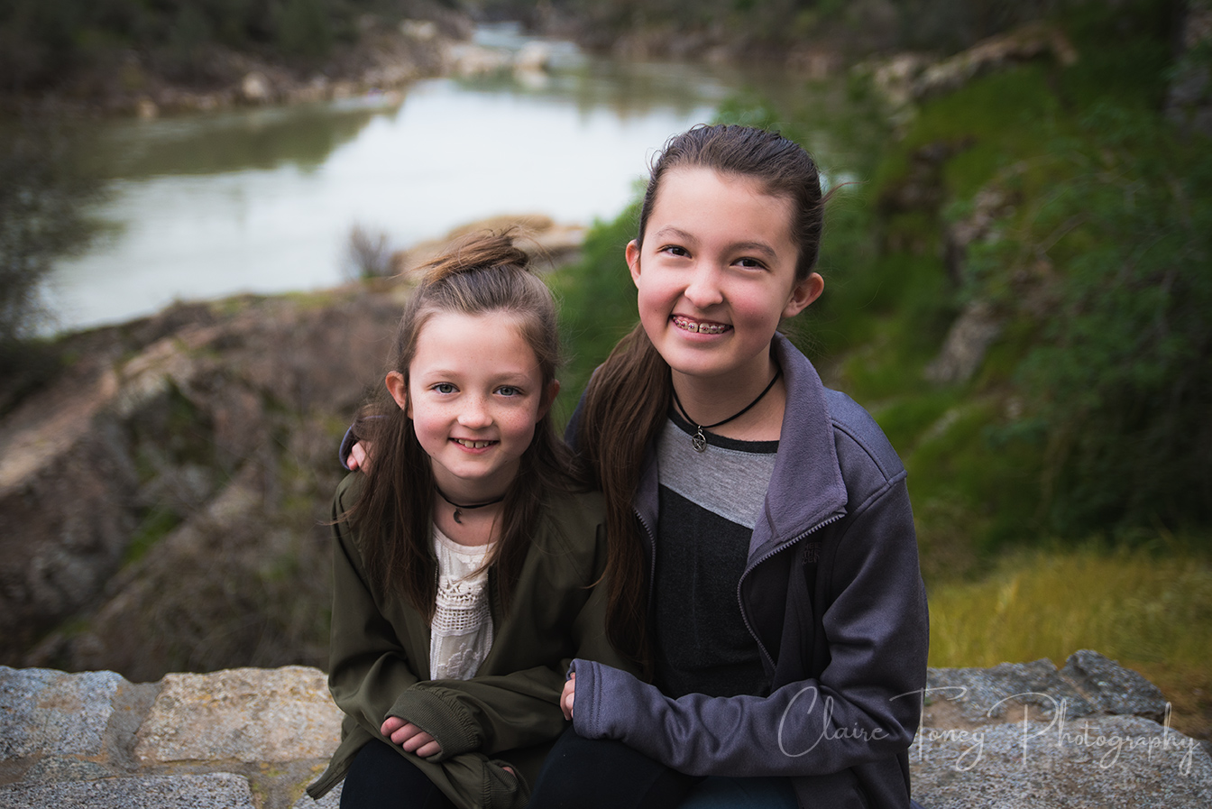 tween sisters sitting in lookout area with view of Folsom Rainbow Bridge behind them