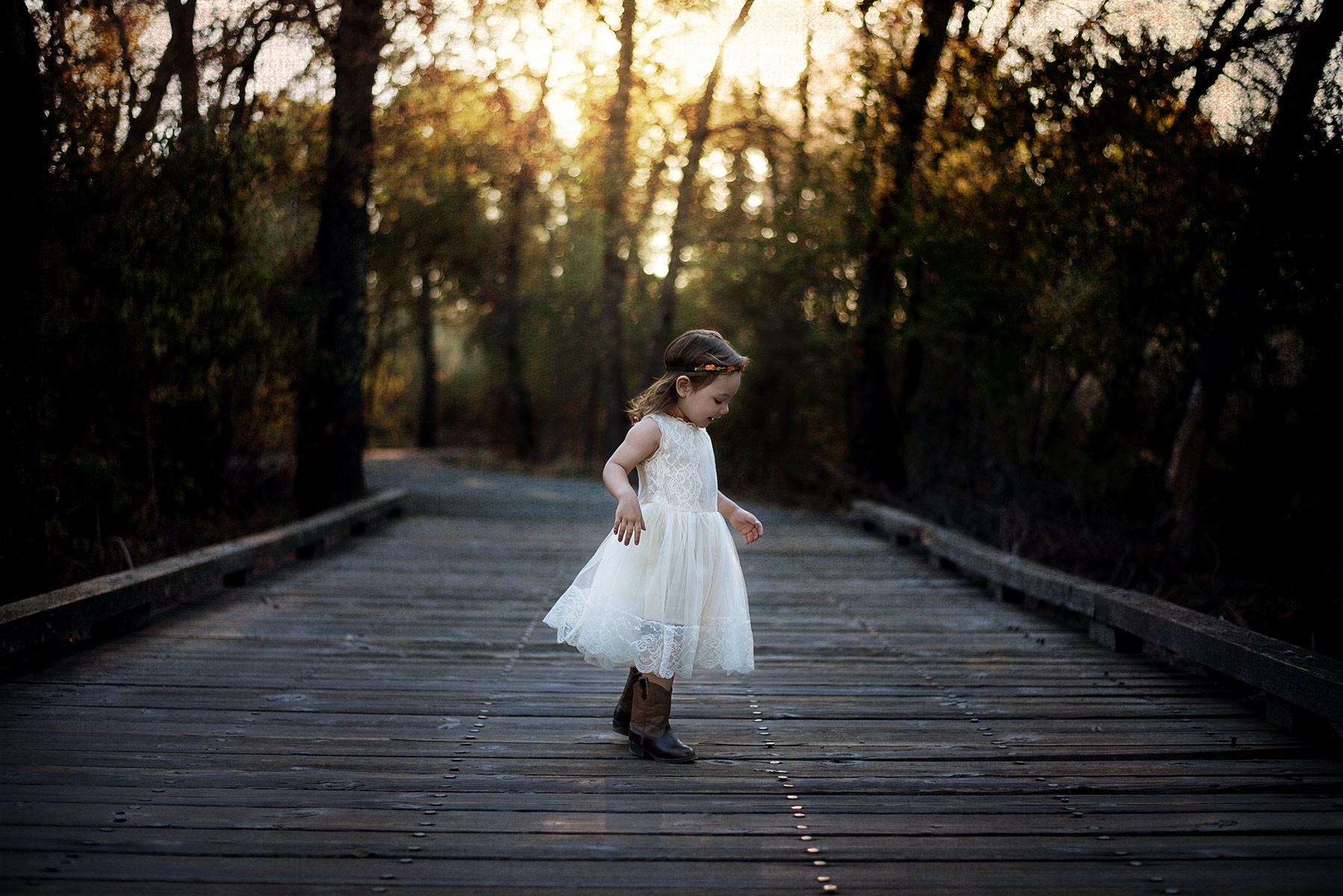 Little girl wearing a vintage style dress with brown cowboy boots during sunset